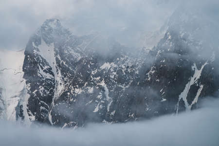 Atmospheric alpine scenery with snowy mountains inside low clouds. Beautiful glacier in cloudy sky. Morning light through clouds. Scenic minimalist landscape with rockies in dense fog in pastel tones.