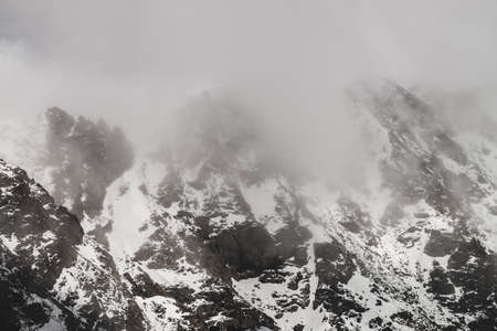 Atmospheric minimalist alpine landscape with snowy rocky mountain peak. Low clouds near snowbound range. Rocks with snow in mist. Craggy mountains in fog. Majestic misty foggy scenery on high altitude