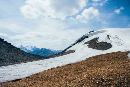 Wonderful view to small glacier on stony hill under blue sky with clouds. Beautiful alpine landscape with ice cornice on rock. Colorful mountain scenery on high altitude. Majestic highland nature.