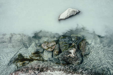 Nature background with mossy stones on silver water of mountain river. Silver sand on sandy bottom of mountain river. Shine on milky river surface. Gray nature backdrop with clear water with sand. 스톡 콘텐츠