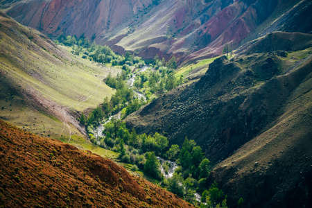 Beautiful mountain river and green trees in valley between multicolor clay hills. Scenic landscape with mountain creek in colorful canyon and vivid multi-color mountains. Picturesque mountains scenery
