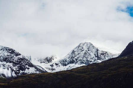 Wonderful view to great mountains with snow on tops and glaciers. Dramatic landscape with snowy mountains under cloudy sky. Atmospheric alpine scenery with snow on rocky mountains in overcast weather.