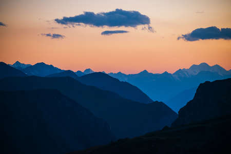 Colorful dawn landscape with beautiful mountains silhouettes and golden gradient sky with blue clouds. Vivid mountain scenery with picturesque multicolor sunset. Scenic sunrise view to mountain range.