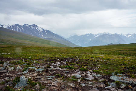 Beautiful view from pass to great snowy mountains under cloudy gray sky. Dramatic alpine landscape with snow mountains in rainy weather. Atmospheric scenery with giant mountain ridge in overcast day. 스톡 콘텐츠