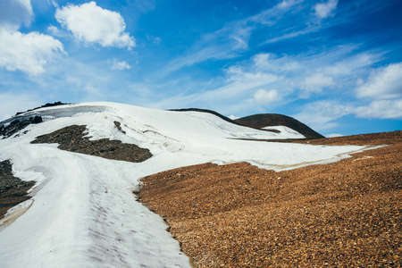 Beautiful small glacier with ice cornice on stony hill under cloudy sky. Snow on mountain. Firn on rock. Atmospheric alpine scenery on high altitude. Wonderful highland landscape of majestic nature. 스톡 콘텐츠