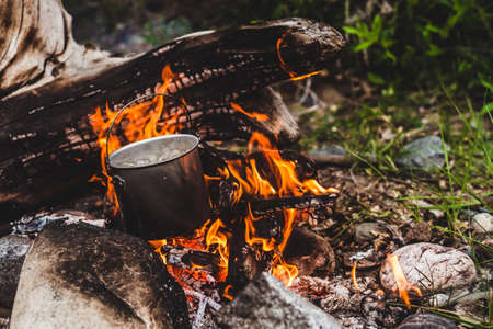 Kettle stands on fire. Cooking food at fire in wild. Beautiful big log burns in bonfire close-up. Survival in wild nature. Wonderful flame with caldron. Pot is on flames. Campfire background.