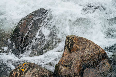 Full frame nature background with boulders in water riffle of mountain river. Powerful water stream of mountain creek. Textured backdrop of fast flow of mountain brook with rapids. Big stones close-up