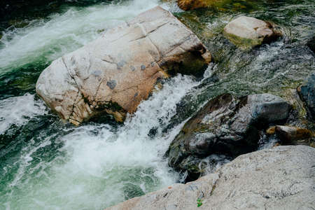 Nature background with cascades of mountain creek close-up. Scenic landscape with beautiful mountain brook with green water. Idyllic scenery with green water in small river. Fast water flow closeup.