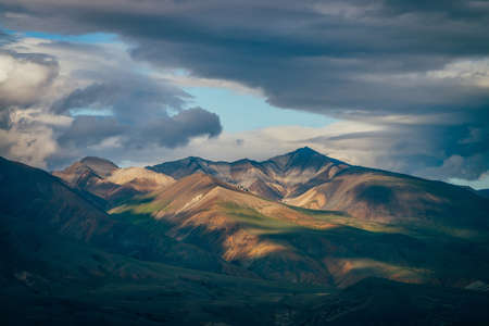 Awesome highland landscape with great mountains and blue clearance in cloudy sky in overcast weather. Blue skylight in cloudy sky above huge multicolor mountains in sunlight. Colorful mountain scenery 스톡 콘텐츠