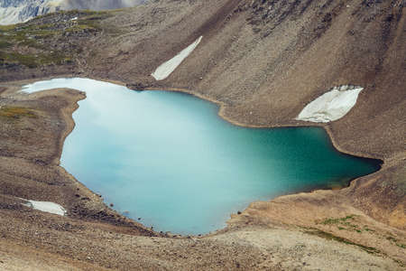 Atmospheric minimalist alpine landscape with beautiful glacial lake in highland valley among rocky mountains. Pieces of snow around mountain lake among stony rocky slope of glacier. Wonderful scenery. 스톡 콘텐츠