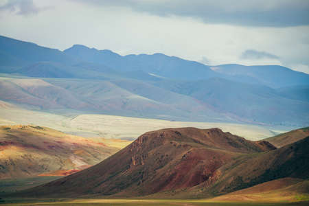 Fantasy vast landscape with vivid multicolor mountains in sunlight. Magenta rocky hill in scenic mountain valley. Colorful sunny scenery with multi-color mountains. Awesome picturesque mountain relief