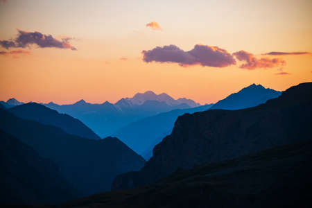 Colorful dawn landscape with beautiful mountains silhouettes and golden gradient sky with lilac clouds. Vivid mountain scenery with picturesque multicolor sunset. Scenic sunrise view to mountain range