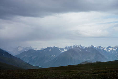 Gloomy view to great snowy mountains under dark gray cloudy sky. Dramatic alpine landscape with snow mountains in rainy weather. Atmospheric scenery with giant mountain ridge in overcast darkness. 스톡 콘텐츠