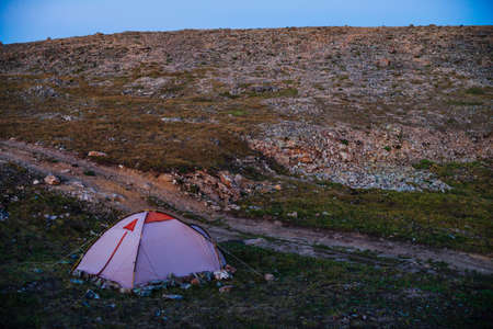 Amazing scenery of twilight in mountains with tent on pass in violet light. Tent near rocky hill in lilac light. Atmospheric mountain landscape with camp on beautiful stony hill. Purple sunset light. 스톡 콘텐츠