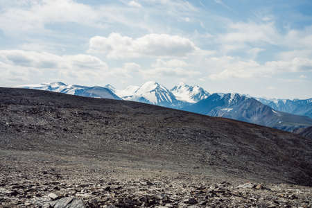 View from stony pass to great mountain range and glacier. Snow on top of giant mountain ridge. Scenic sunny landscape with beautiful big snowy mountains. Snowy peak and glacial mounts under clouds.