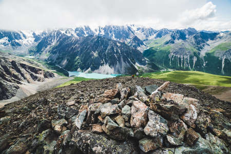 Mountaintop tour on peak overlooking scenic valley with big beautiful mountain lake surrounded by giant rocky ranges and glaciers. Man-made stony pile and people on top. Majestic wilderness nature. Stock Photo