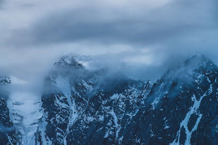 Mysterious dramatic alpine scenery with snowy mountain top inside low clouds in dusk. Bleak view to glacier in cloudy sky in twilight. Atmospheric minimalist landscape with snowy rocks in dense fog. Banque d'images