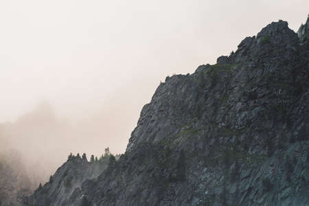 Ghostly atmospheric view to big cliff in cloudy sky. Low clouds among giant rocky mountains. Mysterious place at early foggy morning. Minimalist scenery with beautiful rockies. Dramatic bleak fog.