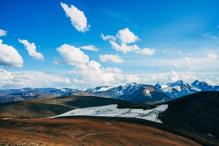 Sunlight in high mountain valley near beautiful glacier on hillside. Sunny view to snowy rocky hill and giant glacial mountain ridge. Colorful alpine landscape. Wonderful scenery on high altitude. 스톡 콘텐츠