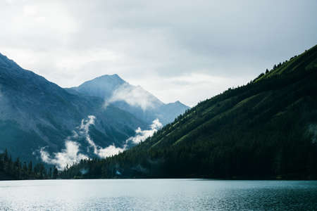 Tranquil alpine landscape with mountain lake near conifer forest on background of giant mountains in overcast weather. Big low cloud above coniferous trees. Mainly cloudy in highlands. Firs over water