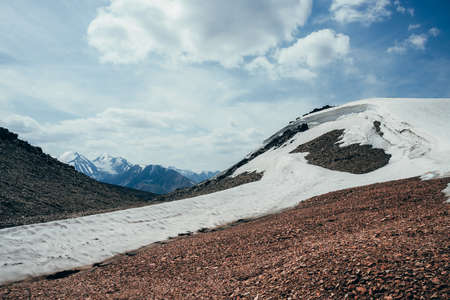 Wonderful view to small glacier on stony hill under blue sky with clouds. Surreal alpine landscape with ice cornice on rock. Surrealistic mountain scenery on high altitude. Majestic highland nature.
