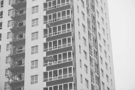Monochrome concept of apartment building under construction close-up. Exterior of new multi-story residential building in grayscale. Background with walls, plastic windows and loggias. Copy space. 스톡 콘텐츠
