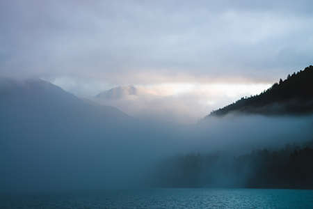Beautiful mountain lake among huge mountains and forest in mist in golden hour. Sun shines through dense low clouds. Big rock glitters at sunrise. Alpine relaxing scenery with fog in pastel tones.