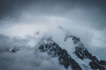 Mysterious dramatic alpine scenery with snowy mountain top inside low clouds in dusk. Bleak view to glacier in cloudy sky in twilight. Atmospheric minimalist landscape with snowy rocks in dense fog.