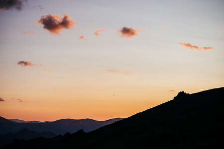Warm gradient of dawn sky above layers of mountain and rock silhouettes. Vivid alpine landscape with dark rockies and orange sunrise sky. Minimalist highland scenery with silhouette of rocky mountains