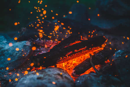 Vivid smoldered firewoods burned in fire close-up. Atmospheric background with orange flame of campfire. Unimaginable full frame image of bonfire. Glowing embers in air. Warm logs, bright sparks bokeh 스톡 콘텐츠