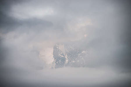 Scenic alpine landscape with snowy mountains inside low clouds at sunrise. Beautiful glacier in dense fog. Soft morning light through clouds. Ghostly scenery with rockies in cloudy sky in pastel tones 스톡 콘텐츠