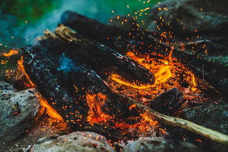 Vivid smoldered firewoods burned in fire close-up. Atmospheric background with orange flame of campfire and blue smoke. Warm full frame image of bonfire. Glowing embers in air. Bright sparks in bokeh