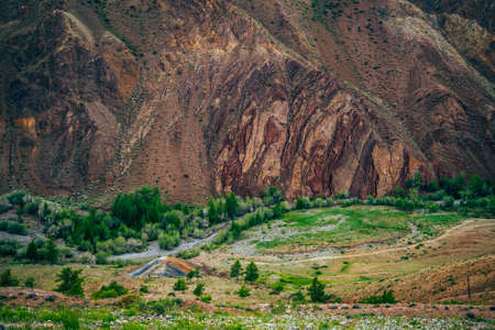 Old mine in valley with small river and green trees between multicolor hills and clay mountain wall. Scenic landscape with colorful canyon and multi-color brown mountains. Picturesque mountain scenery