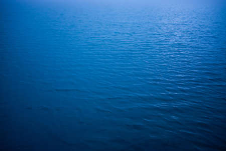 Natural texture of deep blue calm water in sunlight. Wavy sea closeup of blue classic color. Water ripple nature background. Soft light shines on lake surface. Meditative image of clear reflex water.