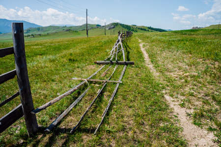 Pathway along broken wood fence and poles with wires in mountains in sunny day. Beautiful sunny alpine landscape with footpath along field behind long fence in highlands. Vivid mountain scenery. 스톡 콘텐츠