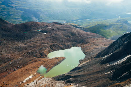 Most beautiful glacial lake of acid green color. Emerald mountain lake and small river in highland valley. Pieces of ice on water among rocks and stones. Awesome alpine lake of unusual green tones.
