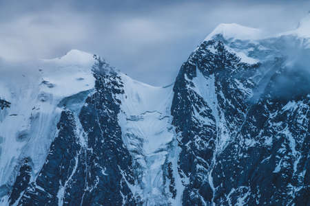 Mysterious dramatic alpine scenery with snowy mountain top inside low clouds in dusk. Bleak view to glacier in cloudy sky in twilight. Atmospheric minimalist landscape with snowy rocks in dense fog. 스톡 콘텐츠