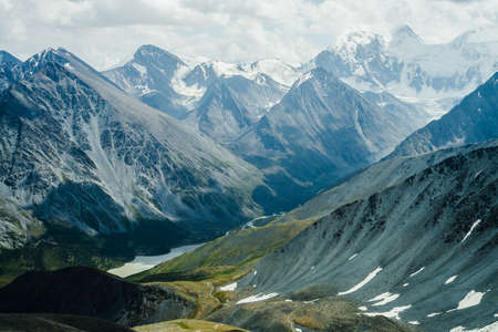 Footpath through hills to beautiful mountain valley with lake. Huge glacier mountains under gray cloudy sky. Awesome dramatic alpine landscape with snow mountains and glaciers. Atmospheric scenery. 스톡 콘텐츠