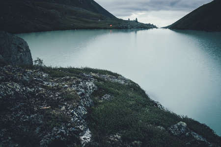 Dark atmospheric landscape with orange tent near mountain lake in highland valley under cloudy sky in dark time. Ripples on mountain lake water in dusk. Dark scenery with water ripple on highland lake
