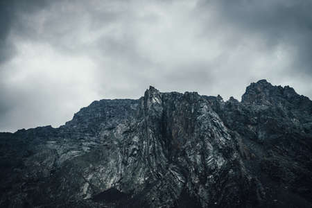 Dark atmospheric landscape with rocky mountain wall under gray cloudy sky. Rocky pinnacle in lead gray cloudy sky. Dark mountain peak in overcast weather. Gloomy minimalist scenery with high mountains