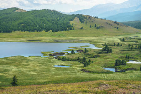 Beautiful green mountain scenery with lake system on tableland among forest hills. Scenic landscape with lakes group on plateau. Blue lakes system and channels in wide valley. System of mountain lakes