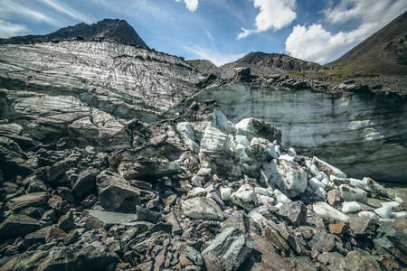 Scenic mountain landscape with big glacier and high top in sunny day. Awesome highland scenery with icy hill with big stones and mountain peak. Glacier ice among moraines. Blocks of ice in sunlight.