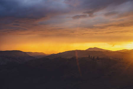 Atmospheric landscape with silhouettes of mountains with trees on background of dawn sky with vivid orange sunlight and sun rays. Colorful nature scenery with sunset or sunrise of illuminating color.