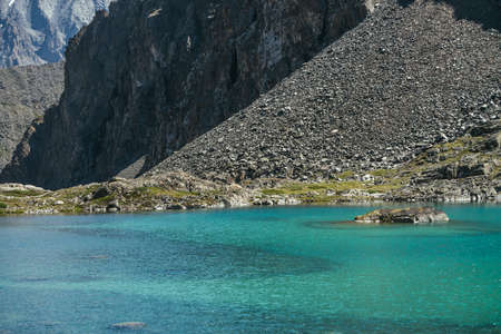 Beautiful scenic landscape with turquoise mountain lake. Azure glacial lake in sunlight. Colorful sunny scenery with clear water surface of mountain lake near big rocky mountain. Glacier lake.