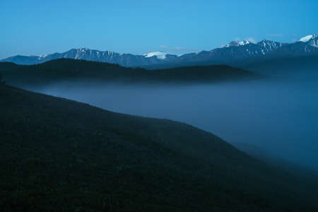 Atmospheric mountains landscape with dense fog and great snow mountain top under twilight sky. Alpine scenery with big snowy mountains over thick fog in night. High snow pinnacle above clouds in dusk.