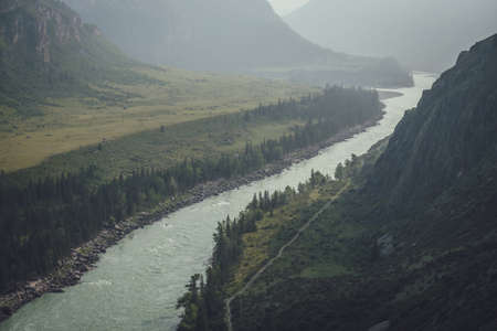 Misty mountain landscape with wide mountain river. Dark green gloomy scenery with confluence of two mountain river in mist. Dark atmospheric view to confluence of great rivers in rainy weather.