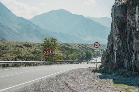 Scenic landscape with speed limit road sign on mountain highway. Side view to tract in highlands. Beautiful scenery with asphalt road with road markings. Highway with solid line and mountain river. Standard-Bild