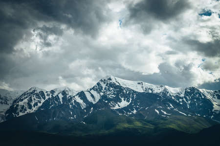 Dramatic mountains landscape with big snowy mountain ridge under cloudy sky. Dark atmospheric highland scenery with high mountain range in overcast weather. Awesome big mountains under gray clouds.