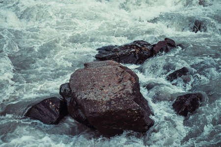 Atmospheric nature background with giant stones in mountain river. Big rocks in powerful water stream closeup. Nature backdrop with big boulders in waves. Dark turquoise mountain river with stones.