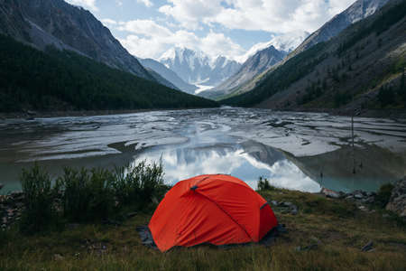 Scenic alpine landscape with orange tent near beautiful mirror mountain lake with streams in highland valley from snowy mountains under cloudy sky. Sunny high mountain scenery with mirror glacial lake
